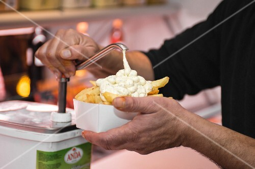 Mayonnaise being added to chips (Brussels, Belgium)