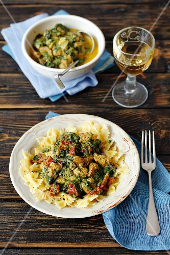 Farfalle with chicken, spinach and dried tomatoes in a creamy curry sauce