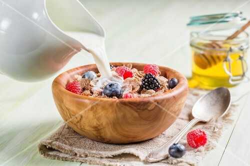 Milk being poured onto wholemeal cornflakes with berries