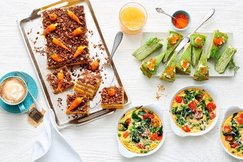 A brunch buffet with carrot cake, green pancake cake and pea frittata in pans