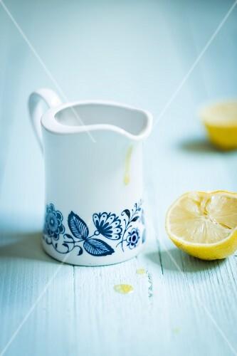 A retro jug of lemon dressing next to a juiced lemon half