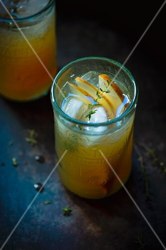 Rum punch cocktail with thyme and pear