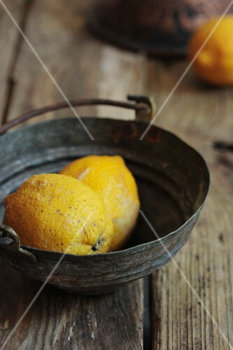 Lemons in a metal bowl on a rustic wooden surface