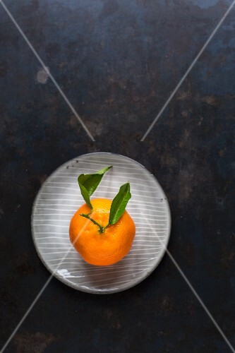 A clementine with leaves on a plate on a dark surface