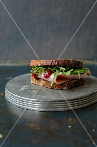 A ham sandwich with rocket and barbecue sauce