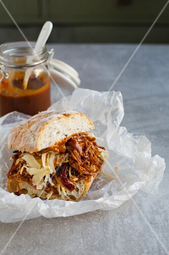 A pulled pork sandwich with coleslaw and barbecue sauce