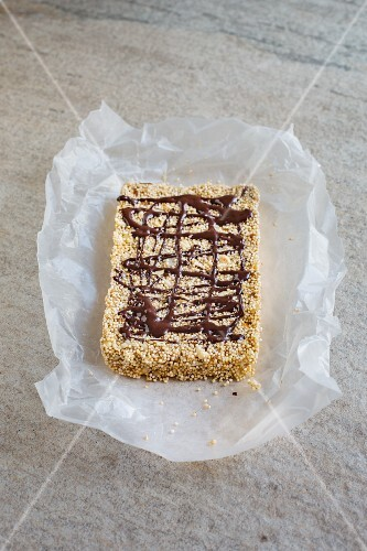 An amaranth bar with chocolate and cashew nuts on a piece of paper