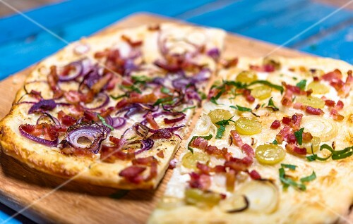 Tarte flambée with two different toppings on a wooden board