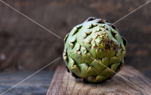 An artichoke on a wooden board