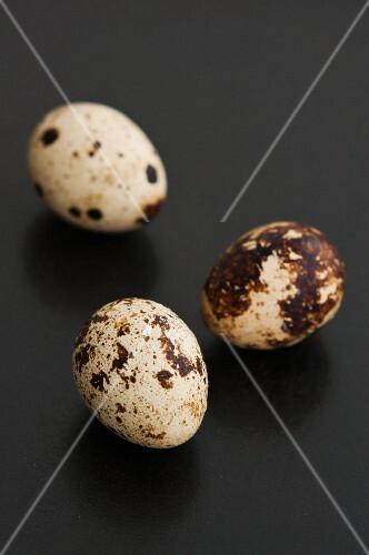 Three quail's eggs on a black surface