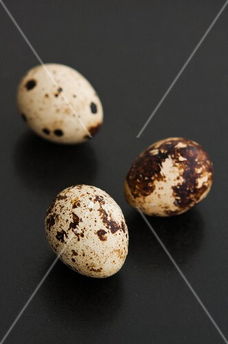 Three quail's eggs on a black surface