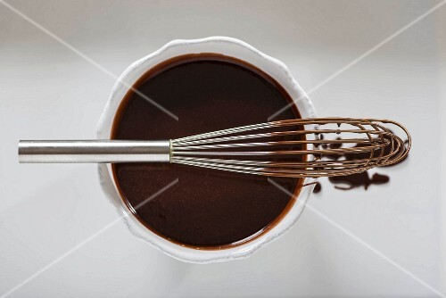 A bowl of chocolate ganache and a chocolate-covered whisk (seen from above)