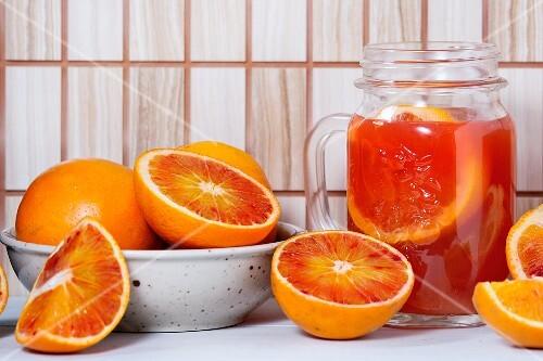 An arrangement of blood oranges and a carafe of blood orange juice
