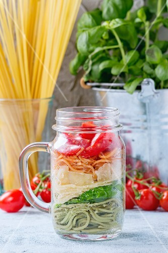 Colourful spaghetti with tomatoes, basil and cheese in a glass