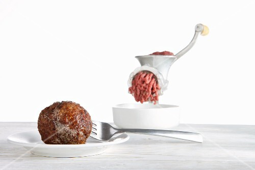 A fried meatball and raw meat in a mincer