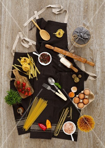 Ingredients and cooking utensils for pasta dishes on an apron