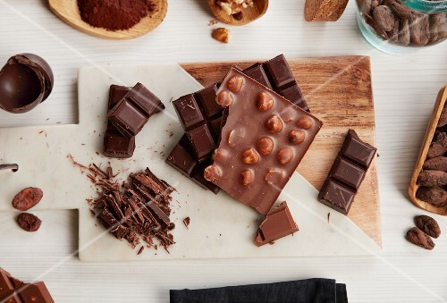 An arrangement of various bars of chocolate and cocoa beans