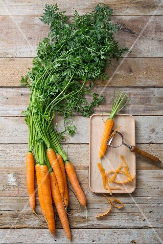 Fresh carrots next to a carrot on a chopping board with a vegetable peeler