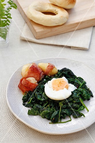 Poached egg on a bed of spinach with bacon-wrapped potatoes