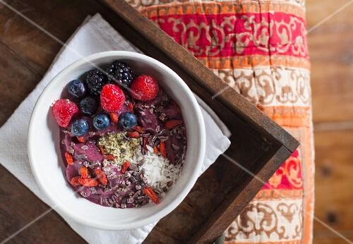 Homemade organic berry yoghurt with fresh fruit, coconut, and gogi berries