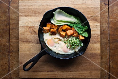 Organic fried eggs with bok choy, sweet potatoes and cress in a pan