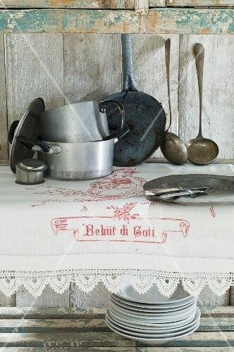 Vintage crockery and embroidered white tablecloth with lace trim on rustic wooden dresser