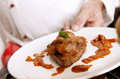 A chef holding a steak on a plate