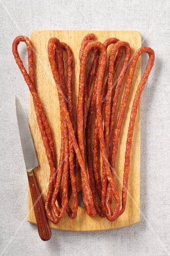 Long thin salami on a wooden board