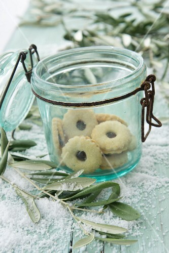Jam sandwich biscuits in an old flip-top jar with olive sprigs and snow