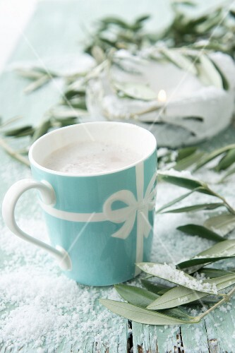 Hot chocolate with milk foam between olives sprigs on a table covered with snow