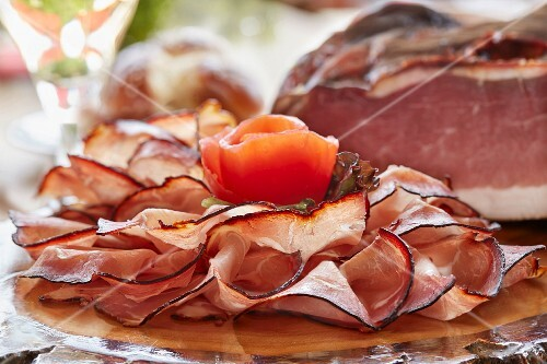 A platter of ham garnished with a tomato rose