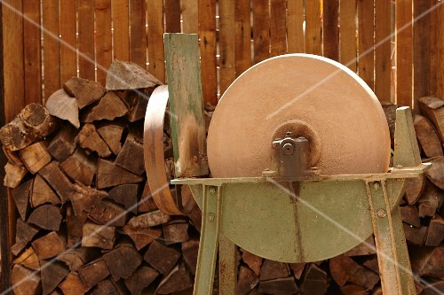 A grinding machine in front of a stack of wood