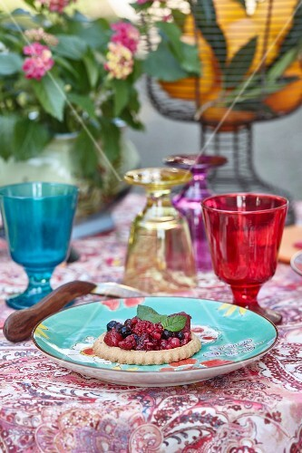 Berry tart on summery table outside