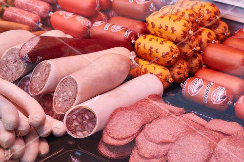Various sausages and sliced meat on display