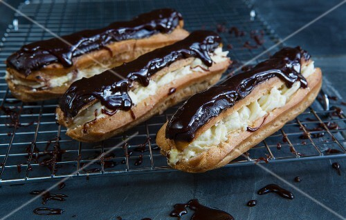 Chocolate eclairs filled with cream and topped with chocolate glaze on a wire rack