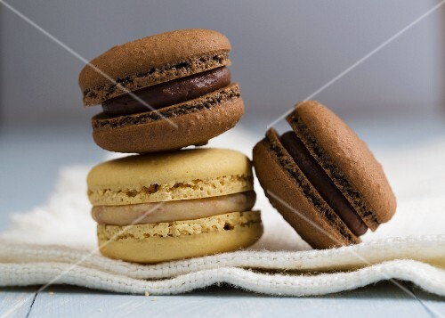 Three macaroons: two chocolate and one vanilla (close-up)