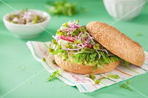 A bagel with cucumber, avocado, radish sprouts and radishes