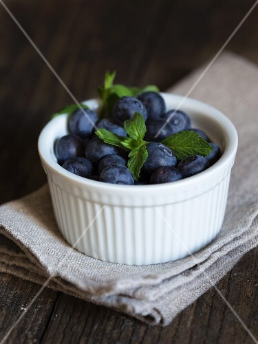 Blueberries with mint in a bowl on a tea towel