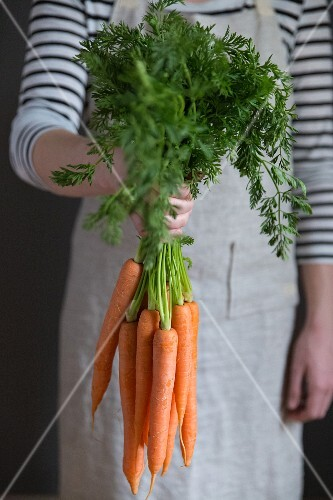 A woman holding a bundle of carrots