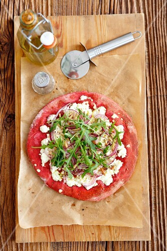 Red pizza with sheep cheese, rocket and red onions