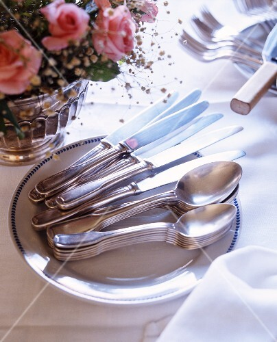Silver cutlery on a white plate next to a bunch of roses in a silver vase