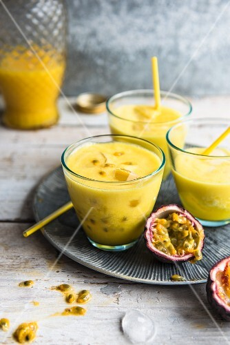 Three glasses of passion fruit smoothie with straws on a grey metal plate
