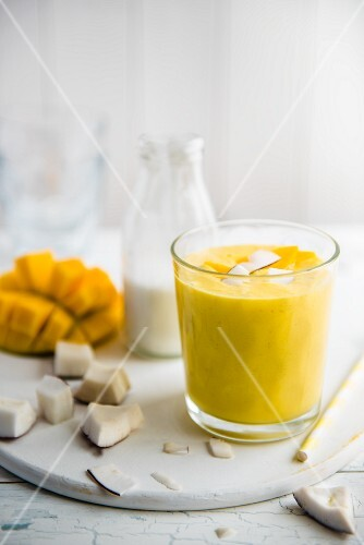 A glass of mango and coconut smoothie with chunks of fresh coconut, coconut milk and mango