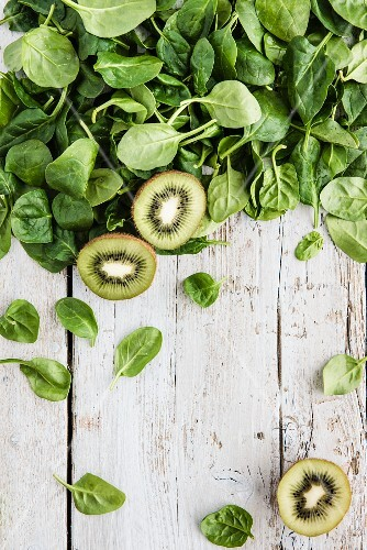 Spinach leaves and kiwis on a white wooden board (seen from above)