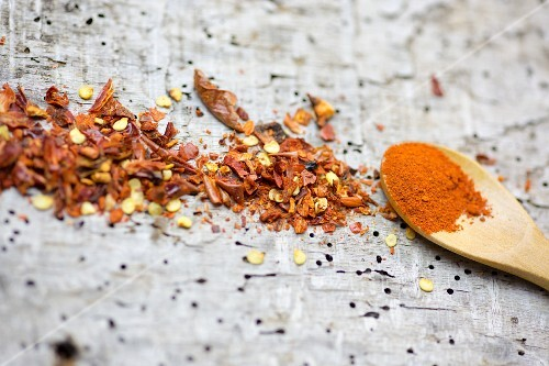 Chilli powder on a wooden spoon and chilli flakes on a wooden surface