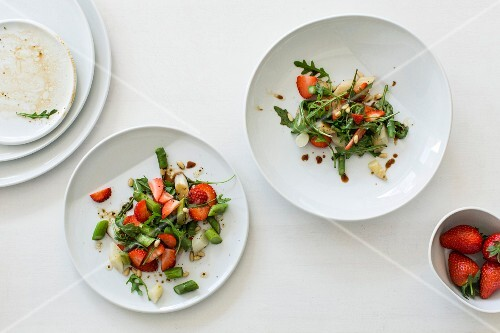 Variations of strawberry and asparagus salad with rocket and green beans