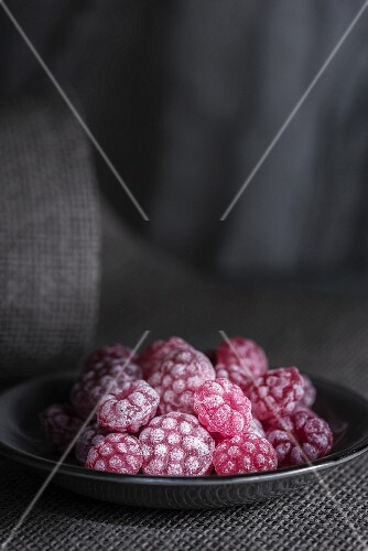Raspberry sweets in a grey plate on a piece of grey fabric