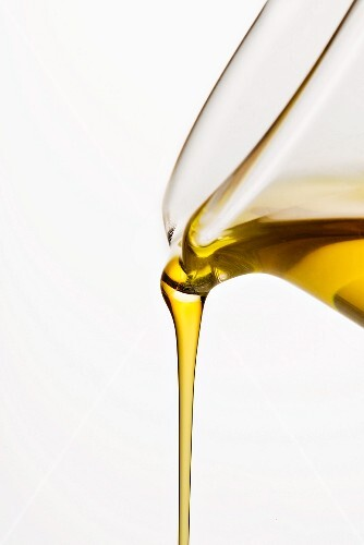 Oil being poured from a carafe against a white background