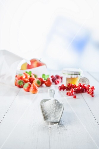 A scoop of sugar on a white wooden surface with arrangement of fruit featuring strawberries, lingonberries and apples in the background