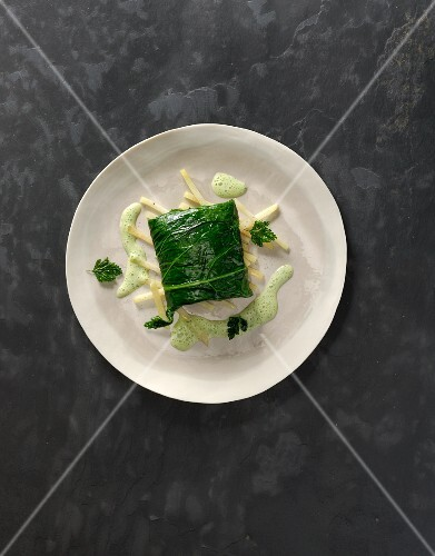 Steamed zander fillet served on a kohlrabi leaf with parsley sauce
